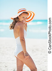 Smiling young woman in hat standing on beach