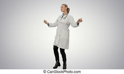 Smiling young woman in lab coat making funny dance on white background.