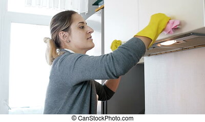 Smiling young woman in latex gloves cleaning cupboards on kitchen with cloth