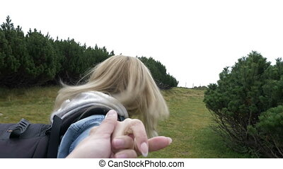 Smiling young woman in love holding hands and leading her boyfriend along alpine trees POV of highland trip concept