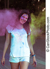 Smiling young woman in nature covered with colorful Gulal powder