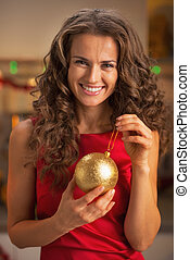 Smiling young woman in red dress holding christmas ball
