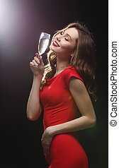 Smiling young woman in red dress with glass of champagne