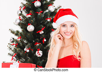 Smiling young woman in santa claus hat near Christmas tree