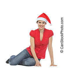 Smiling young woman in Santa hat sitting on floor