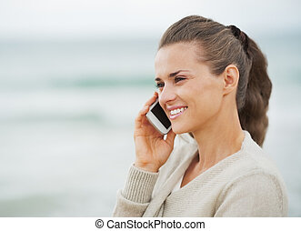 Smiling young woman in sweater on beach talking cell phone
