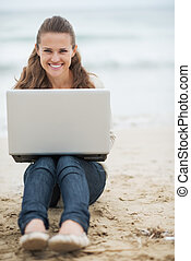 Smiling young woman in sweater sitting on lonely beach