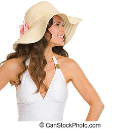 Smiling young woman in swimsuit and hat looking on copy space
