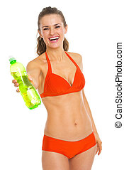 Smiling young woman in swimsuit giving bottle of water