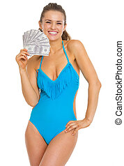 Smiling young woman in swimsuit holding fan of dollars