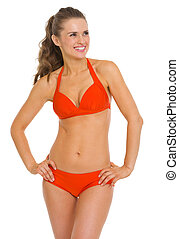 Smiling young woman in swimsuit looking on copy space