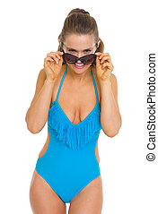 Smiling young woman in swimsuit looking out from sunglasses