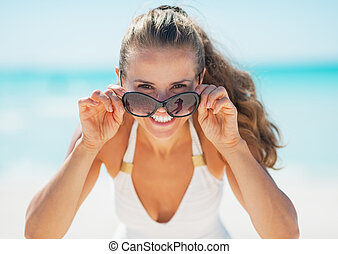 Smiling young woman in swimsuit looking out from sunglasses on beach