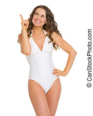 Smiling young woman in swimsuit pointing up on copy space