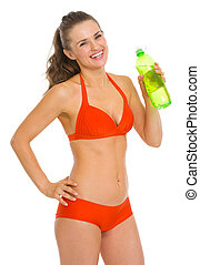 Smiling young woman in swimsuit with bottle of water
