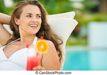 Smiling young woman in swimsuit with cocktail looking on copy space