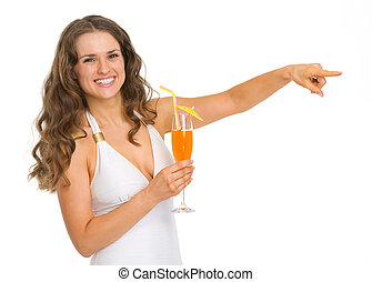 Smiling young woman in swimsuit with cocktail pointing on copy space
