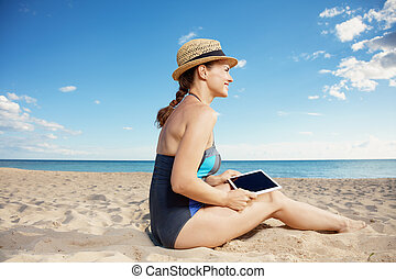 smiling young woman in swimsuit with tablet PC on beach
