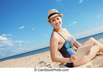 smiling young woman in swimwear with tablet PC on beach