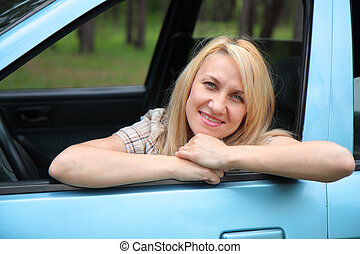 Smiling young  woman in the car