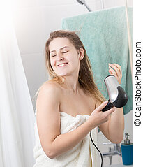 Smiling young woman in towel drying hair at bathroom