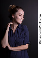 Smiling young woman in trendy clothes, posing on a dark studio background