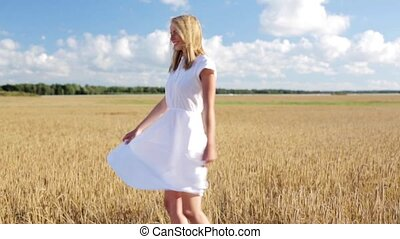 smiling young woman in white dress on cereal field - country...