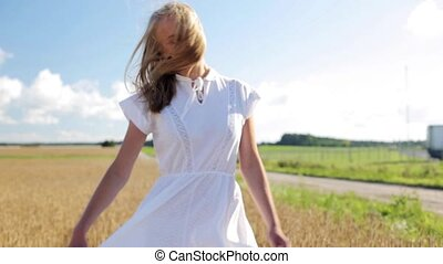 smiling young woman in white dress on cereal field