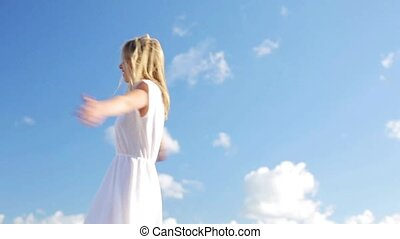 smiling young woman in white dress over blue sky - country,...