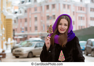 Smiling young woman in winter clothes posing with tasty colorful candies at the city
