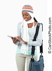 Smiling young woman in winter clothes using her tablet