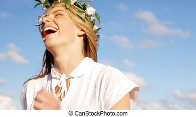 smiling young woman in wreath of flowers laughing -...