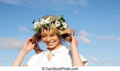 smiling young woman in wreath of flowers outdoors -...