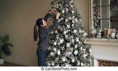 Smiling young woman is decorating green Christmas tree with...