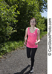 Smiling young woman is jogging outdoors on a sunny summer day.