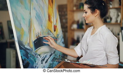 Smiling young woman is painting picture depicting boat and...