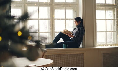 Smiling young woman is reading book sitting on window-sill...