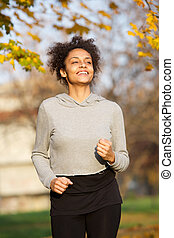 Smiling young woman jogging outdoors in the park