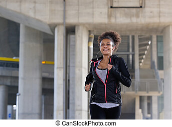 Smiling young woman jogging outdoors