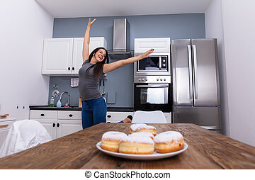 Smiling Young Woman Jumping In The Kitchen