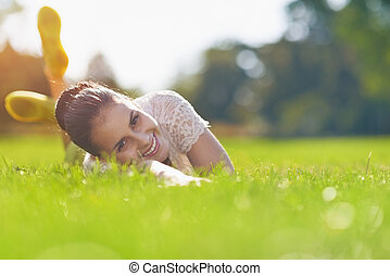 Smiling young woman laying on grass