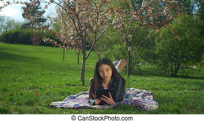 Smiling young woman laying on lawn with tablet pc