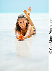 Smiling young woman laying on sea shore and showing shell