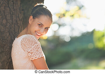 Smiling young woman lean against tree