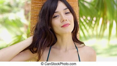 Smiling young woman leaning against a tropical palm tree as she cools off in the shade from the hot summer sun closeup head and shoulders
