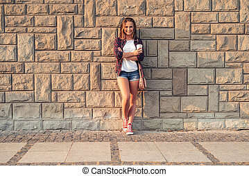 Smiling young woman leaning against a wall in the city