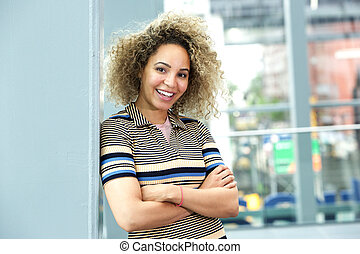 Smiling young woman leaning against wall with arms crossed