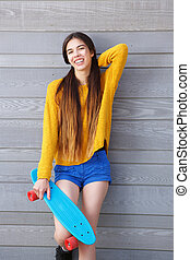 Smiling young woman leaning against wall with skateboard
