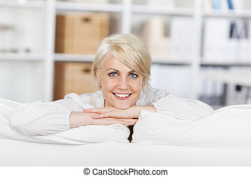 smiling young woman leaning on sofa