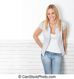 Smiling young woman leaning on white wall